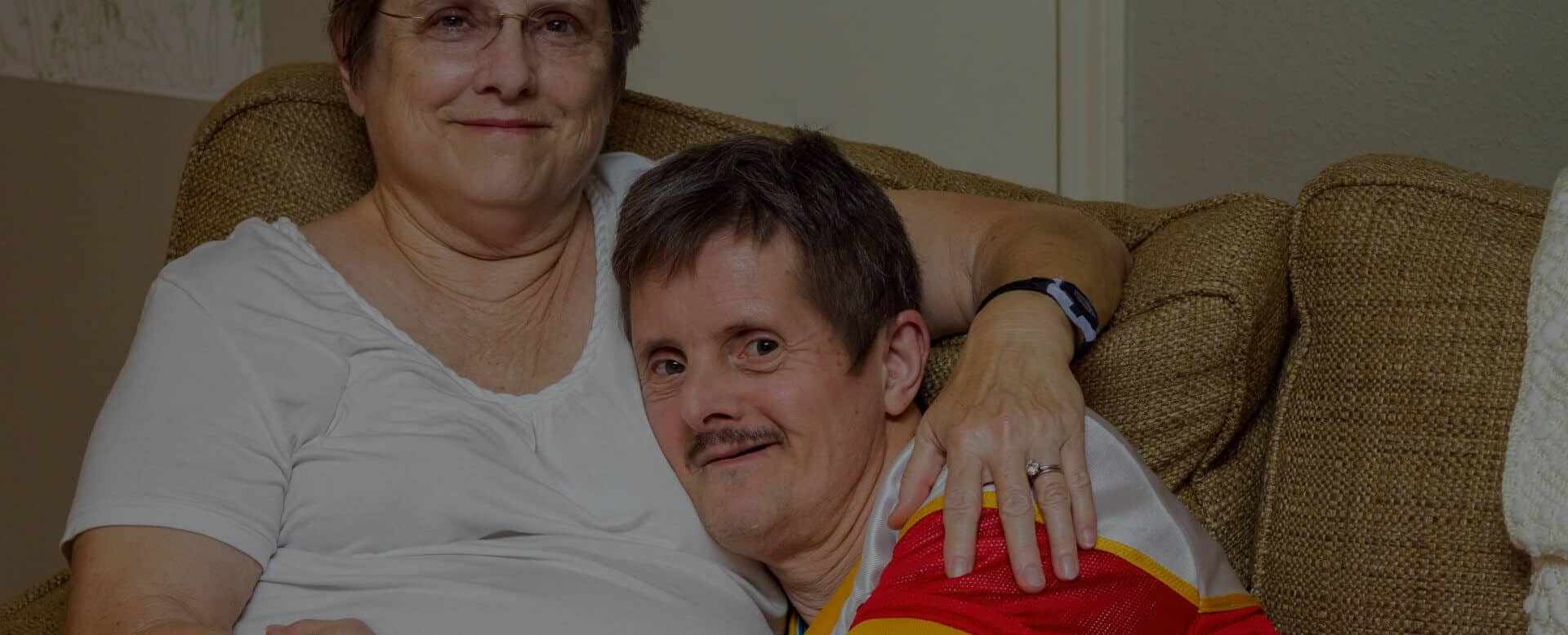 An older men with Downs Syndrome, hugs his older sister