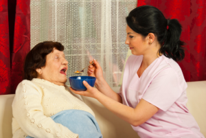 caregiver giving food to the elderly