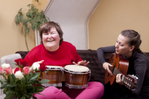 a girl and a person with autism happily playing musical instruments