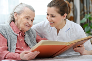 senior woman together with a nurse watching a photo album