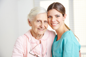 elderly woman with her caretaker smiling